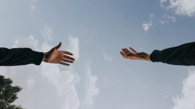 photo of hands reaching for each other